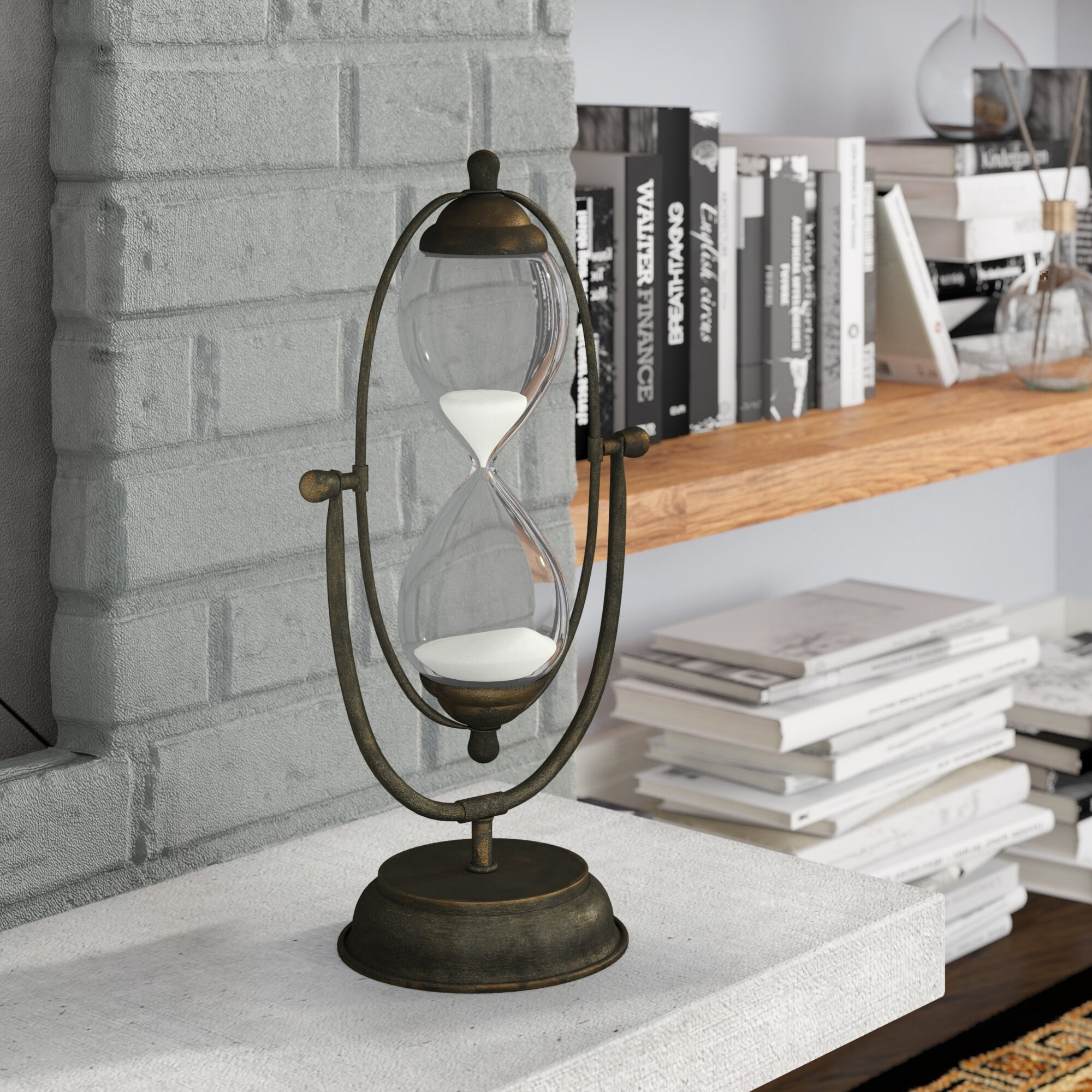 A big hourglass decoration next to a bookcase in front of a fireplace