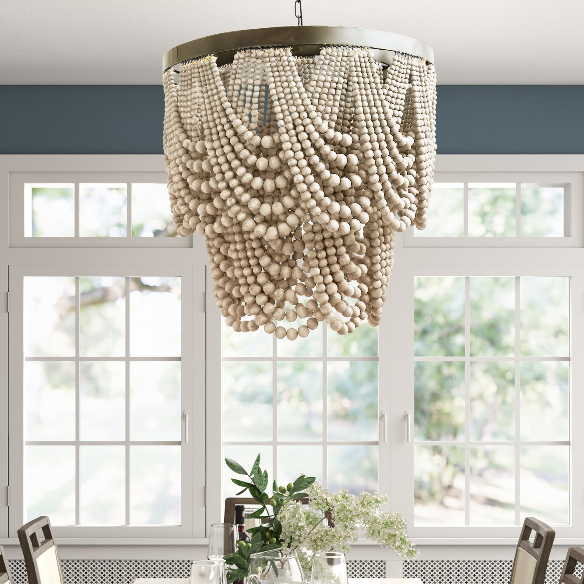 White beaded chandelier hanging on a ceiling above a dining table