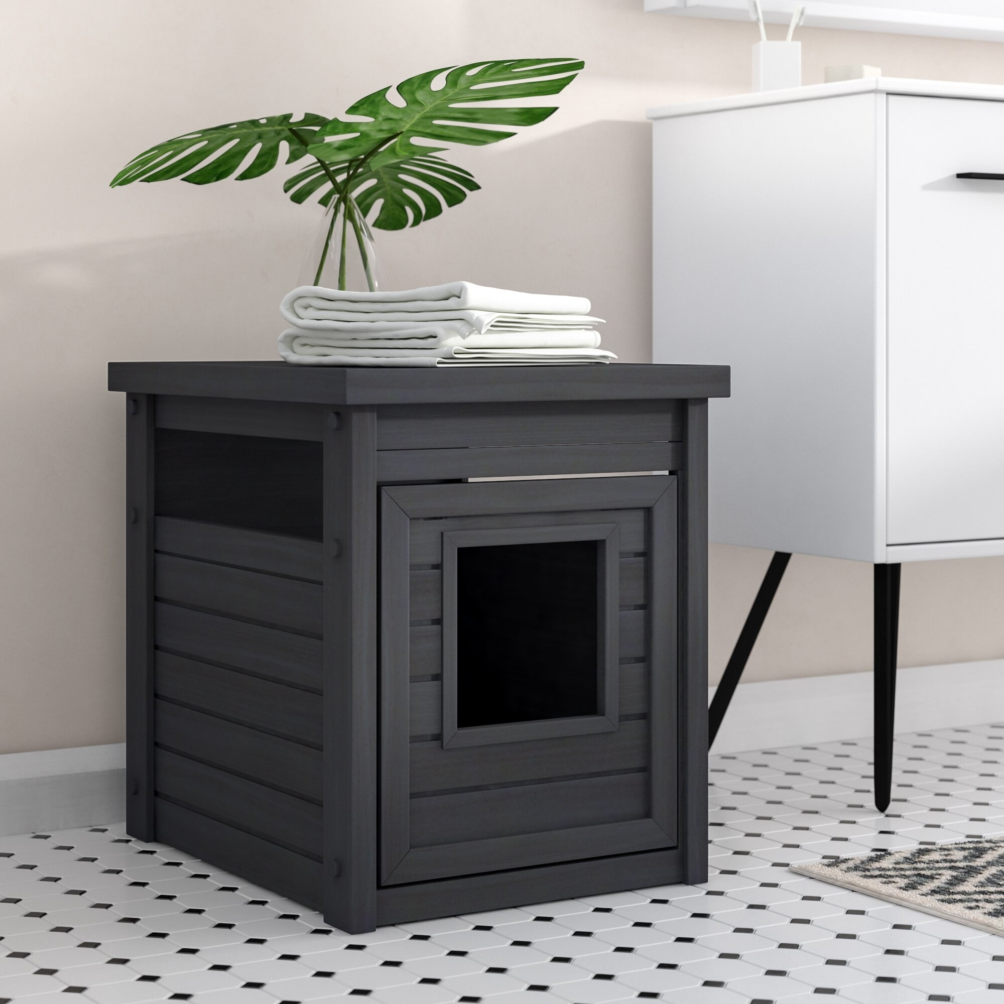 A black litter box that looks like an end table with a plant on top