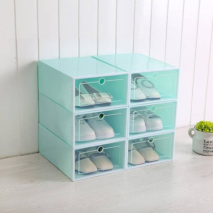 Six teal-colored shoe boxes with clear windows with shoes inside