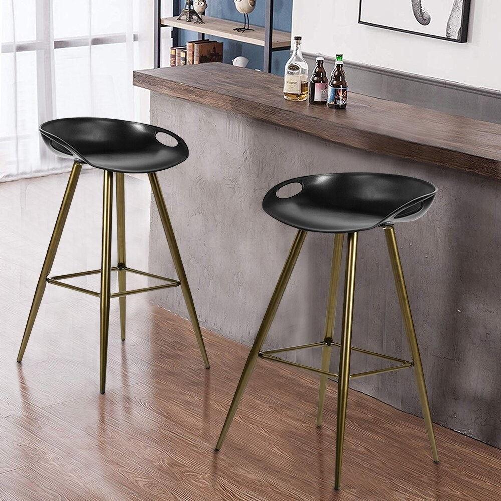 Two black plastic bar stools with golden legs in front of a brown bar