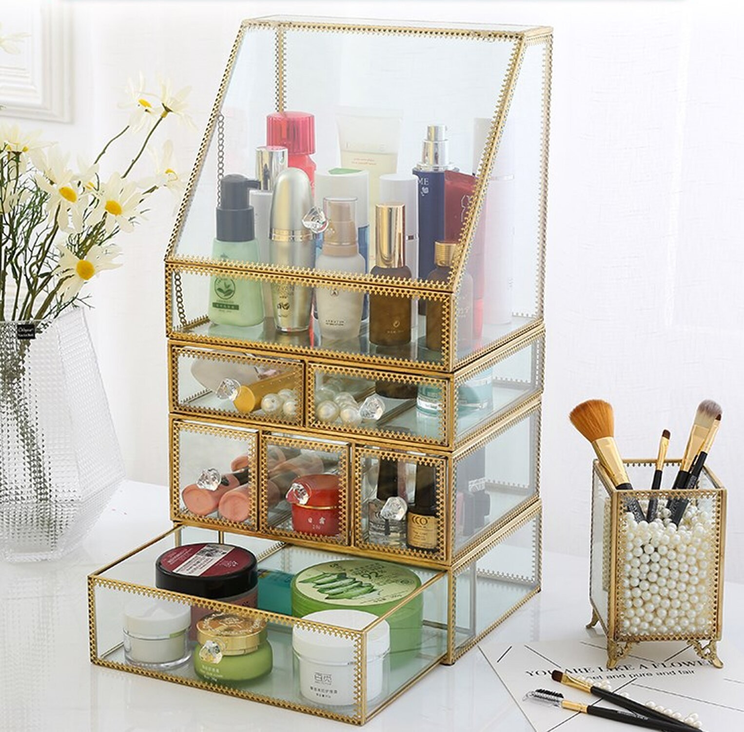 A glamorous makeup organizer that's got several tiers and drawers with makeup and brushes inside and out
