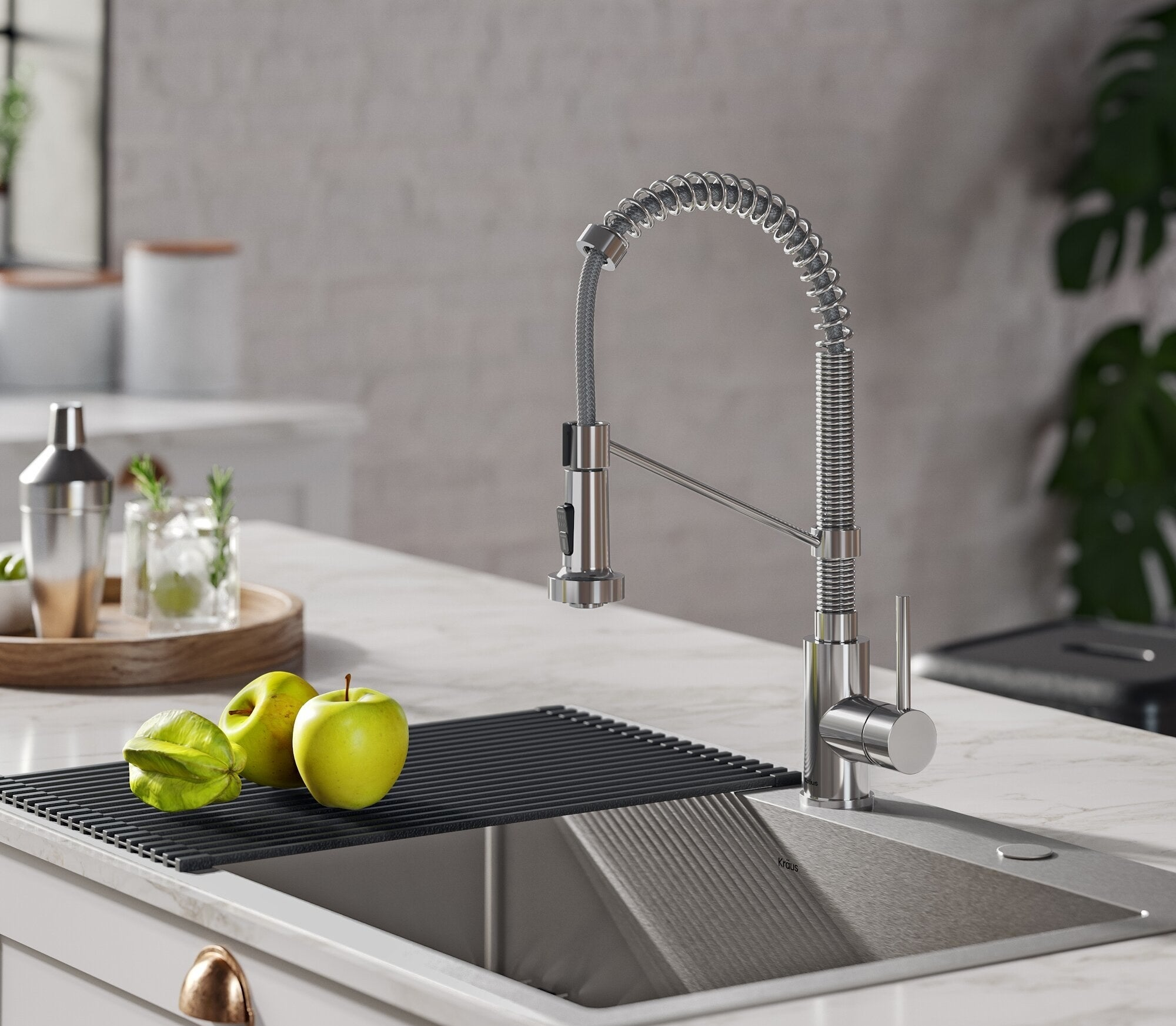 A silver faucet above a sink at a kitchen counter with green apples next to it