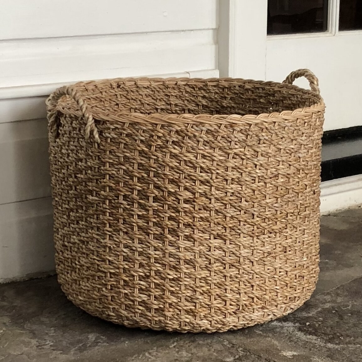 A woven basket outside at a front porch