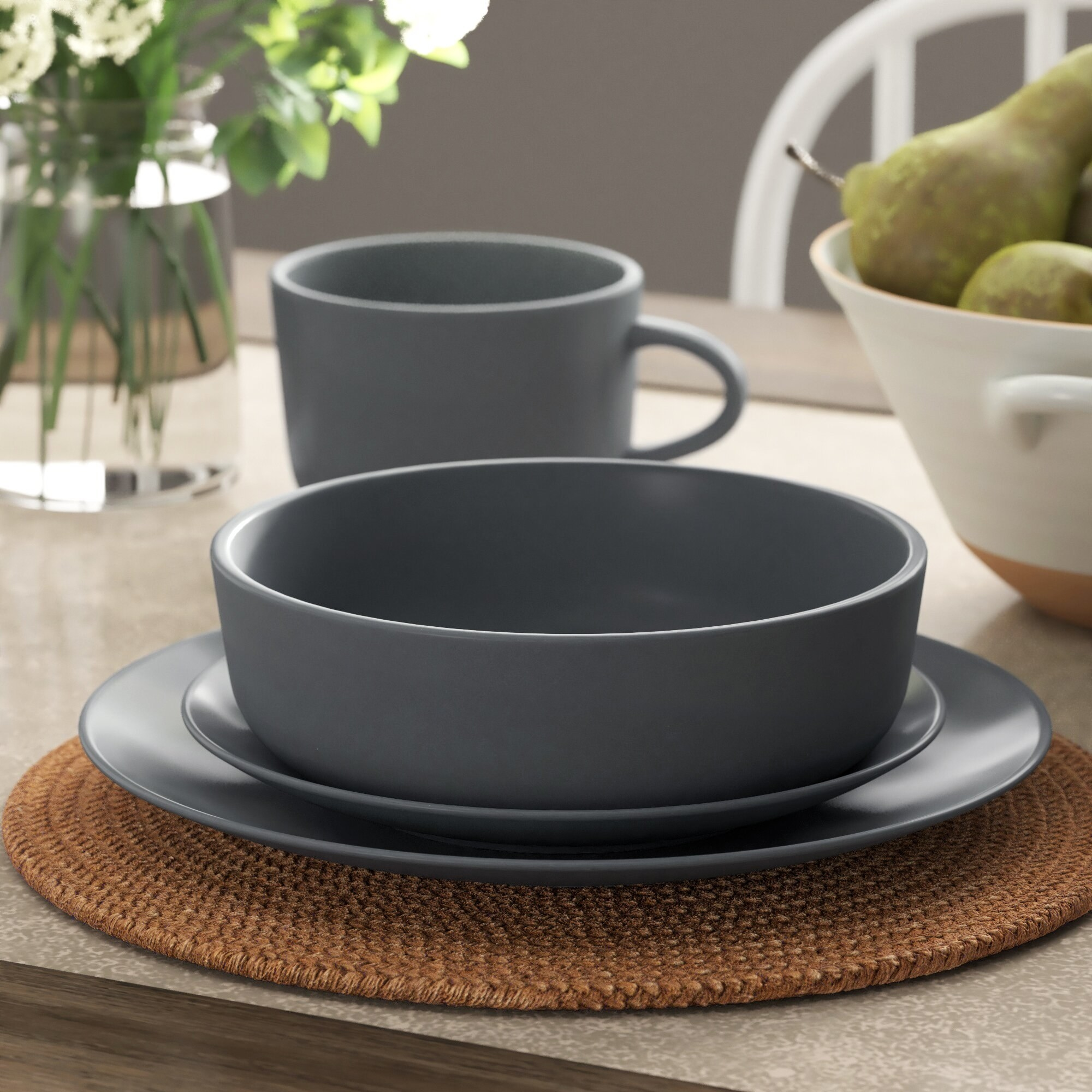 A big gray plate with a little plate and bowl on top and a mug next to it on a dining table