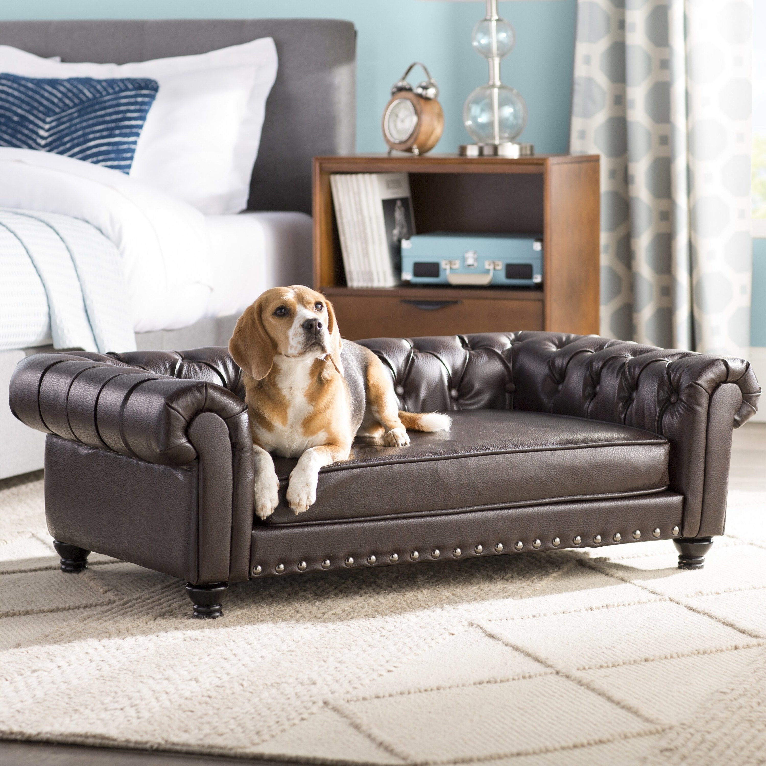 A leather tufted couch that's sized for a dog with a dog sitting on it