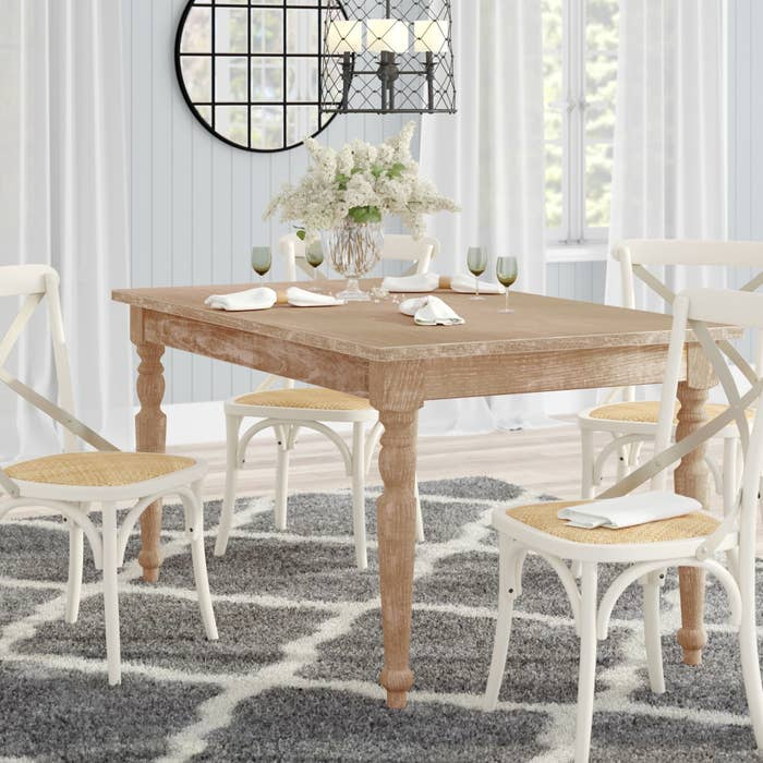 Brown wood farmhouse-style kitchen table with four white chairs around it and a vase of flowers on top