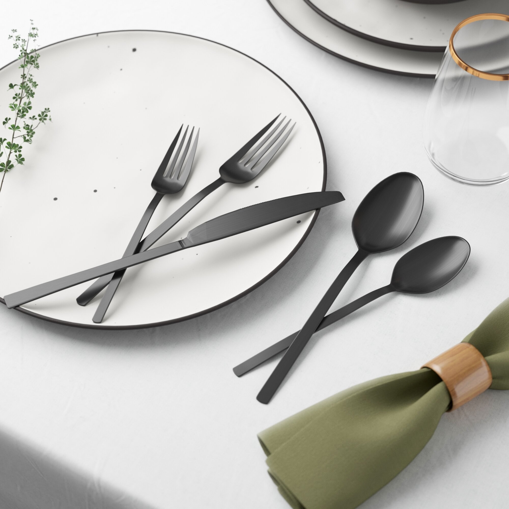 Black forks, spoons and a knife set up on top of a table with a white plate and green napkin