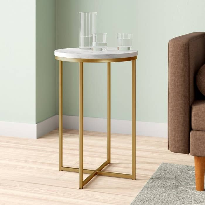 Gold and white side table next to a couch with glasses of water on it