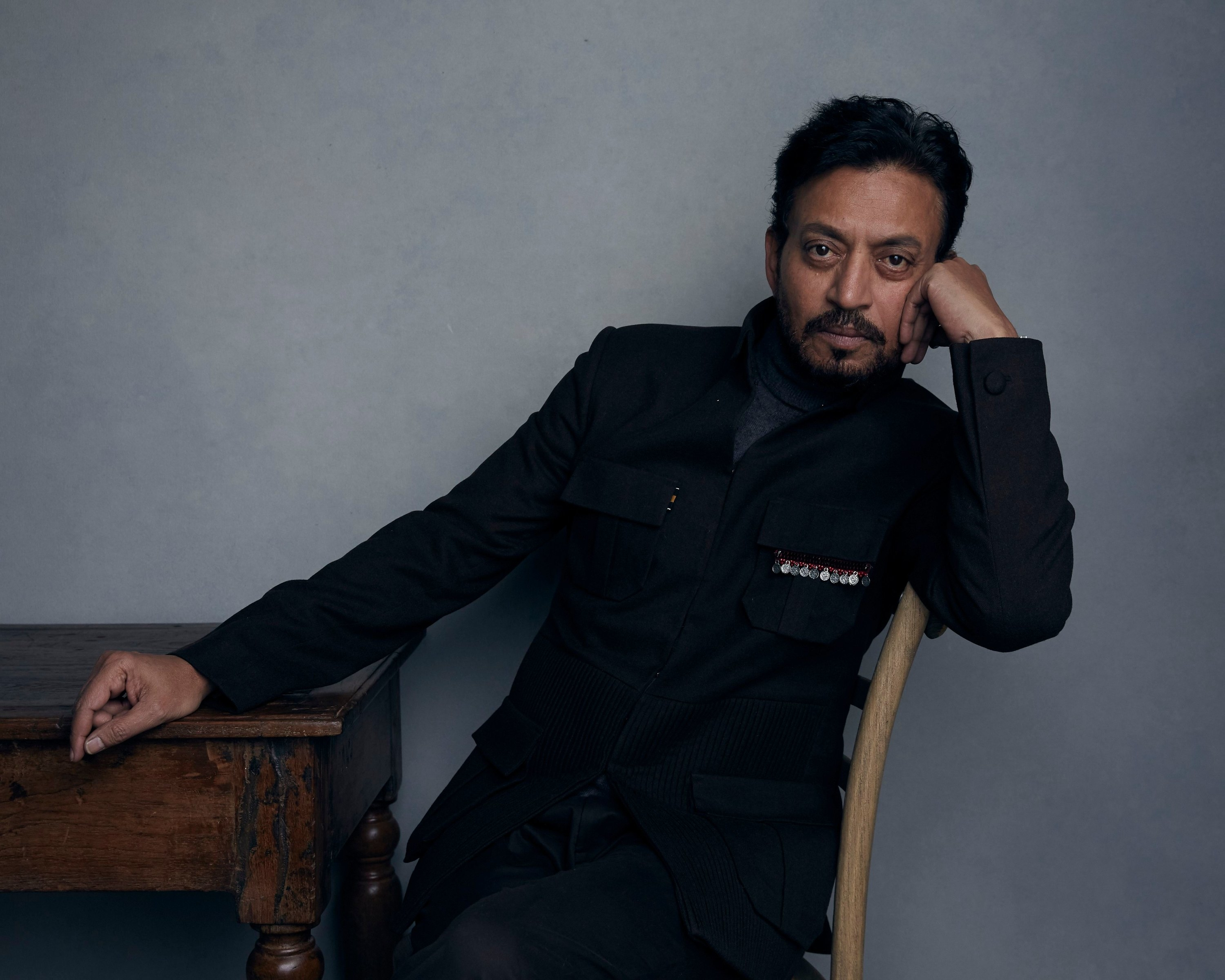 Khan in a black suit seated at a table, staring at the camera