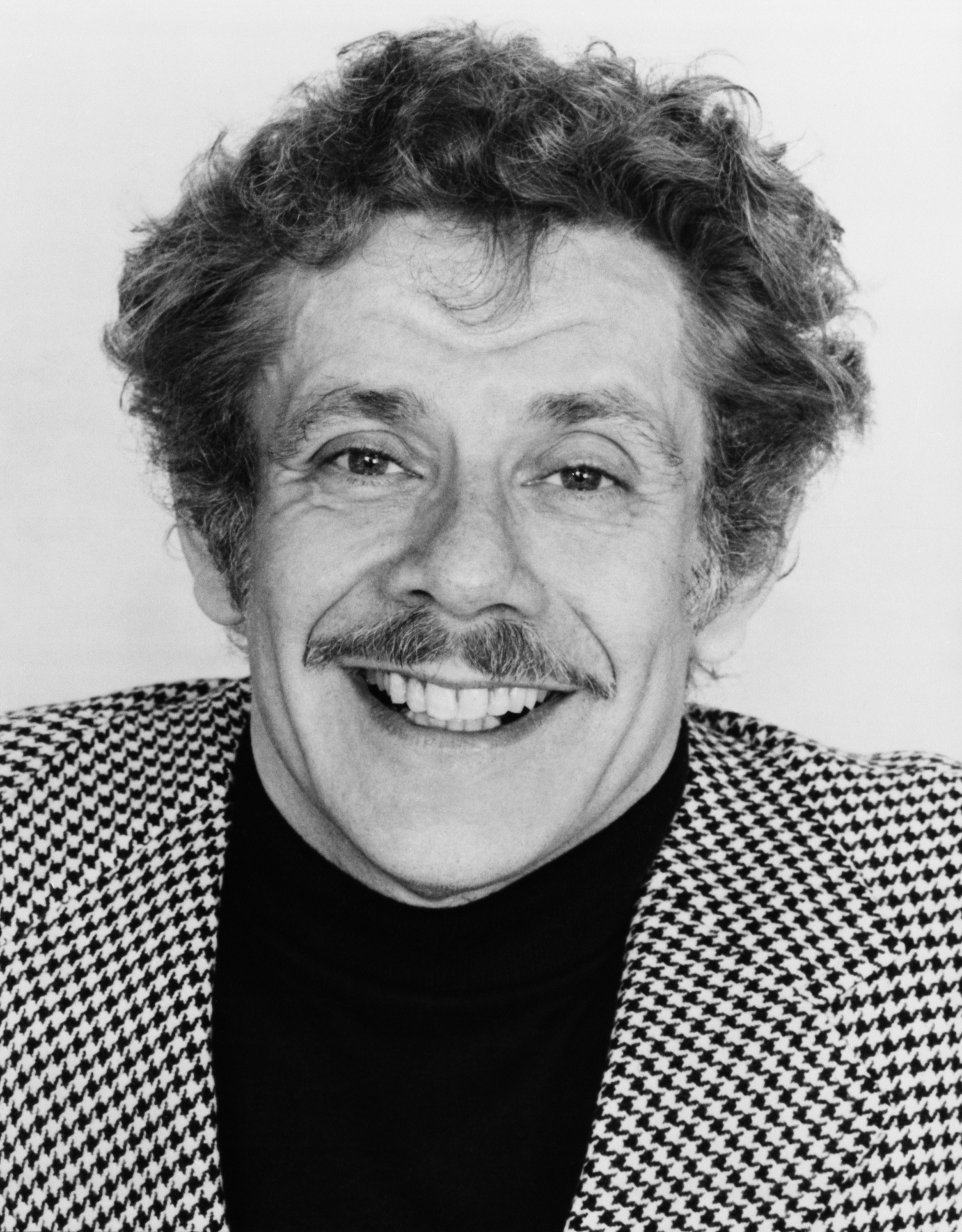 Man with curly hair and a checked suit smiling at camera