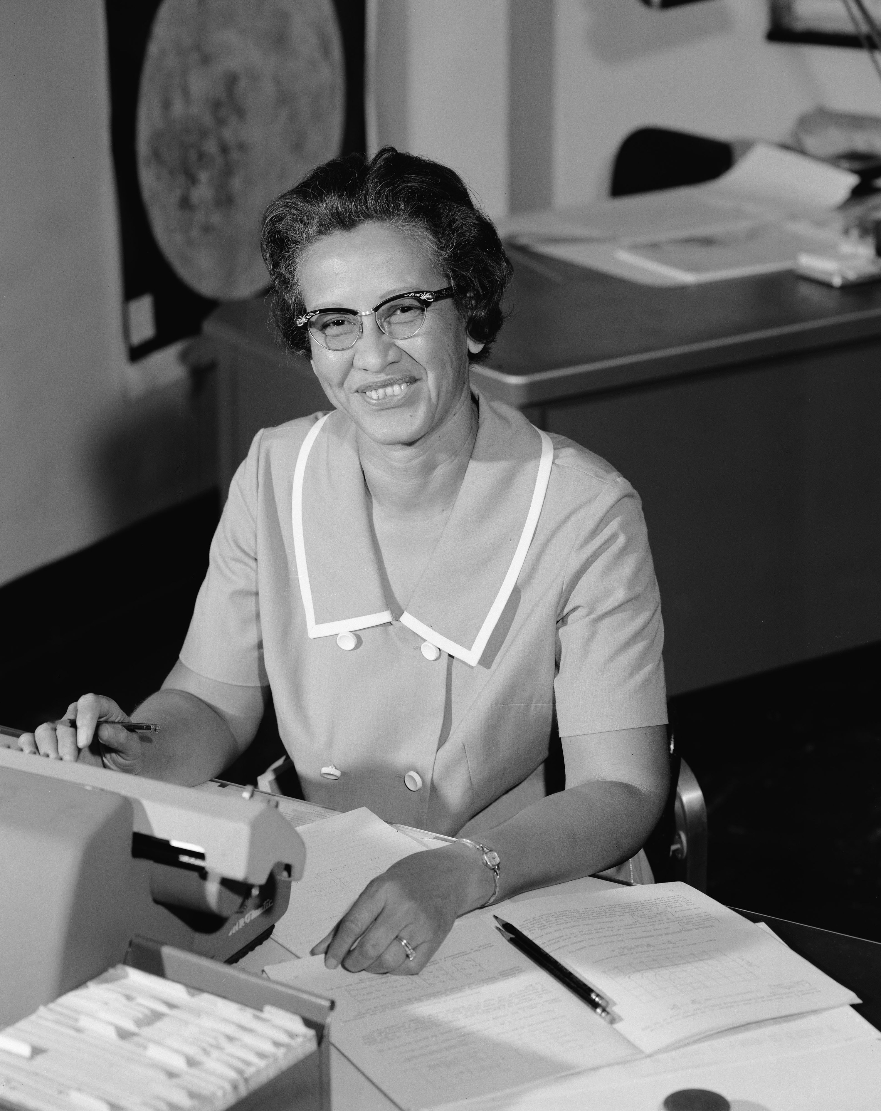 A woman in glasses and a short sleeve suit at a desk with paper, typewriter