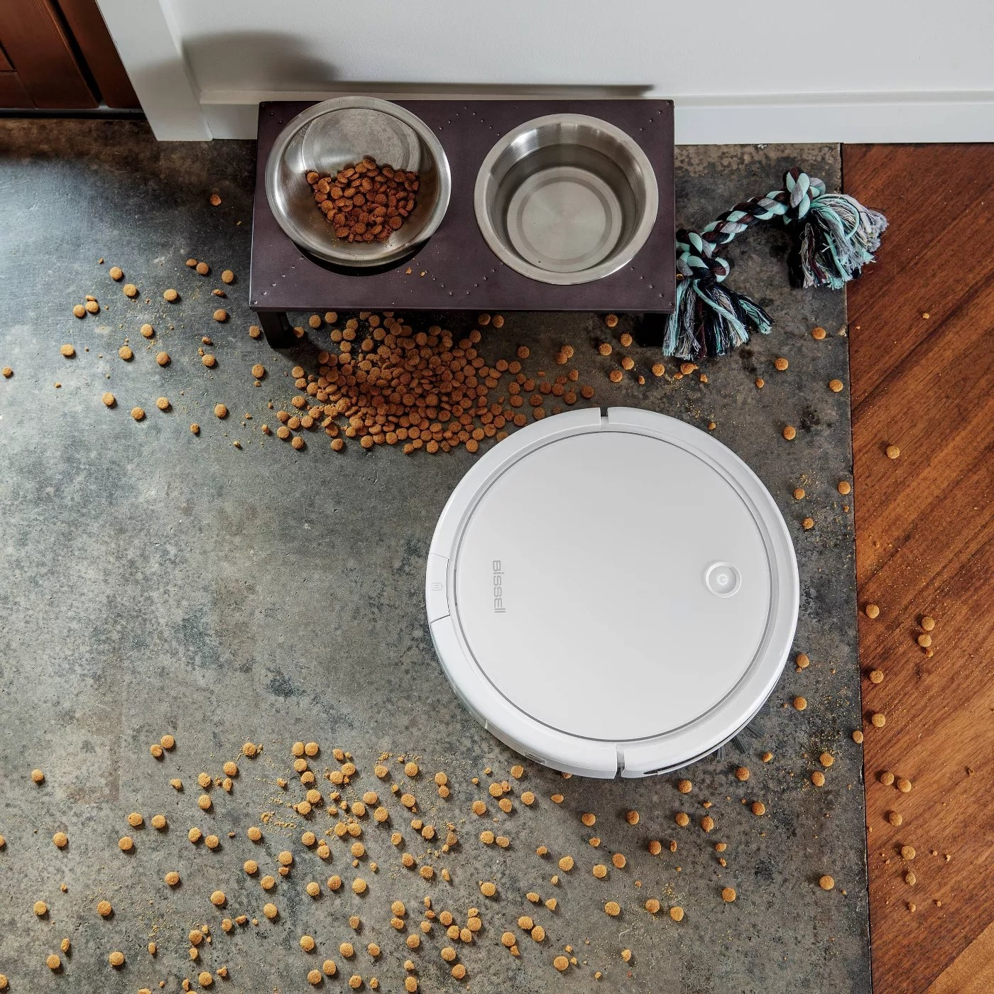 The white BisselL vacuum cleaning up dog food