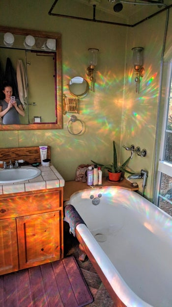 Little rainbows bouncing off walls from iridescent privacy film on bathroom window
