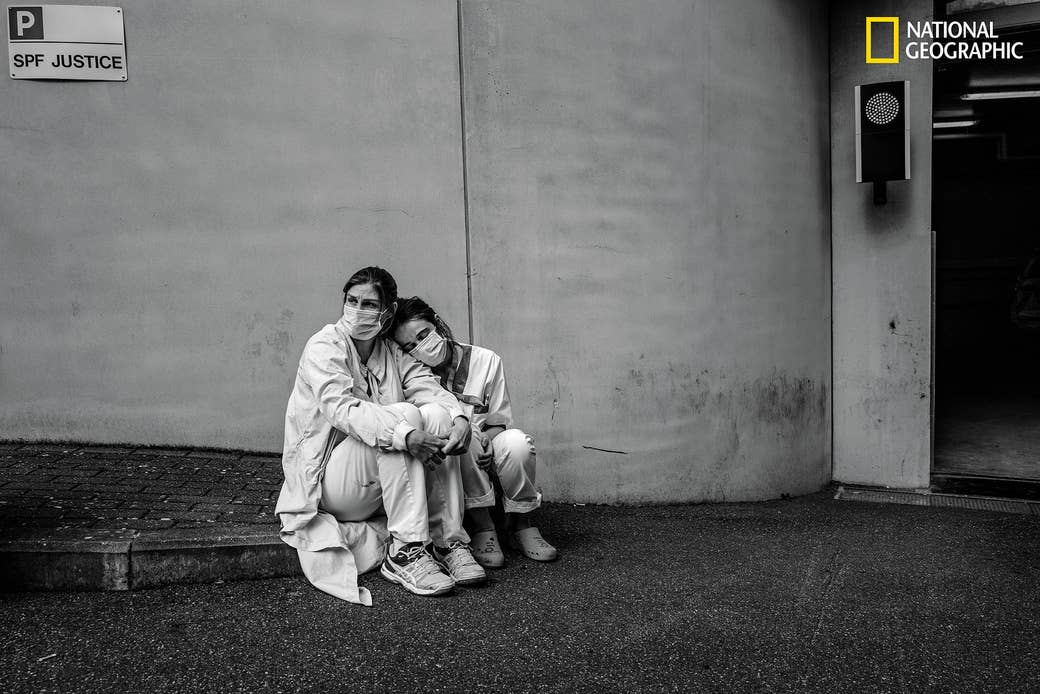 Two nurses in protective gear looking exhausted outside