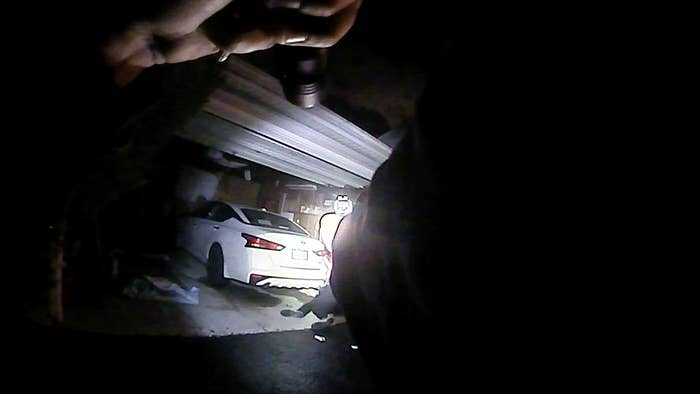 A still from body camera footage shows a police officer pointing a gun and flashlight at a body, which lies on the ground in front of him outside a garage