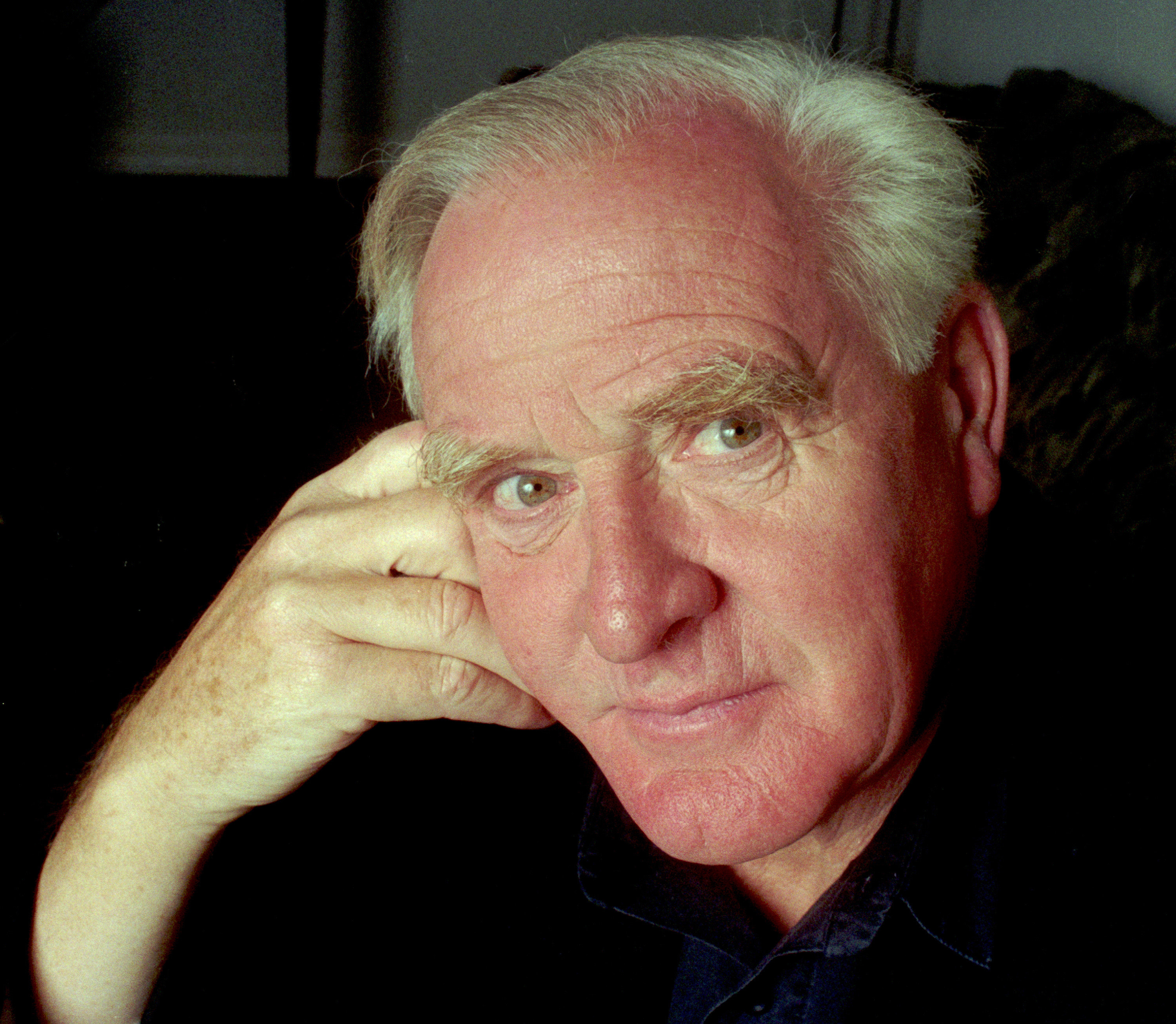 Le Carré, an older man with white hair, posing for the camera