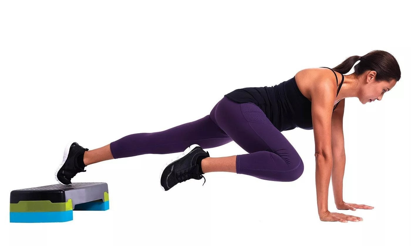 A model using the step desk to do a plank workout