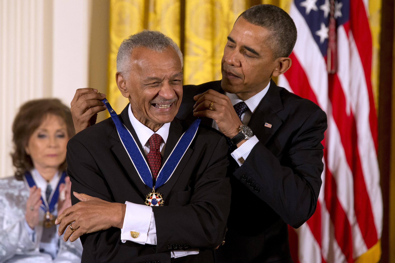 Barack Obama awarding C.T. Vivian an award in front of an American flag