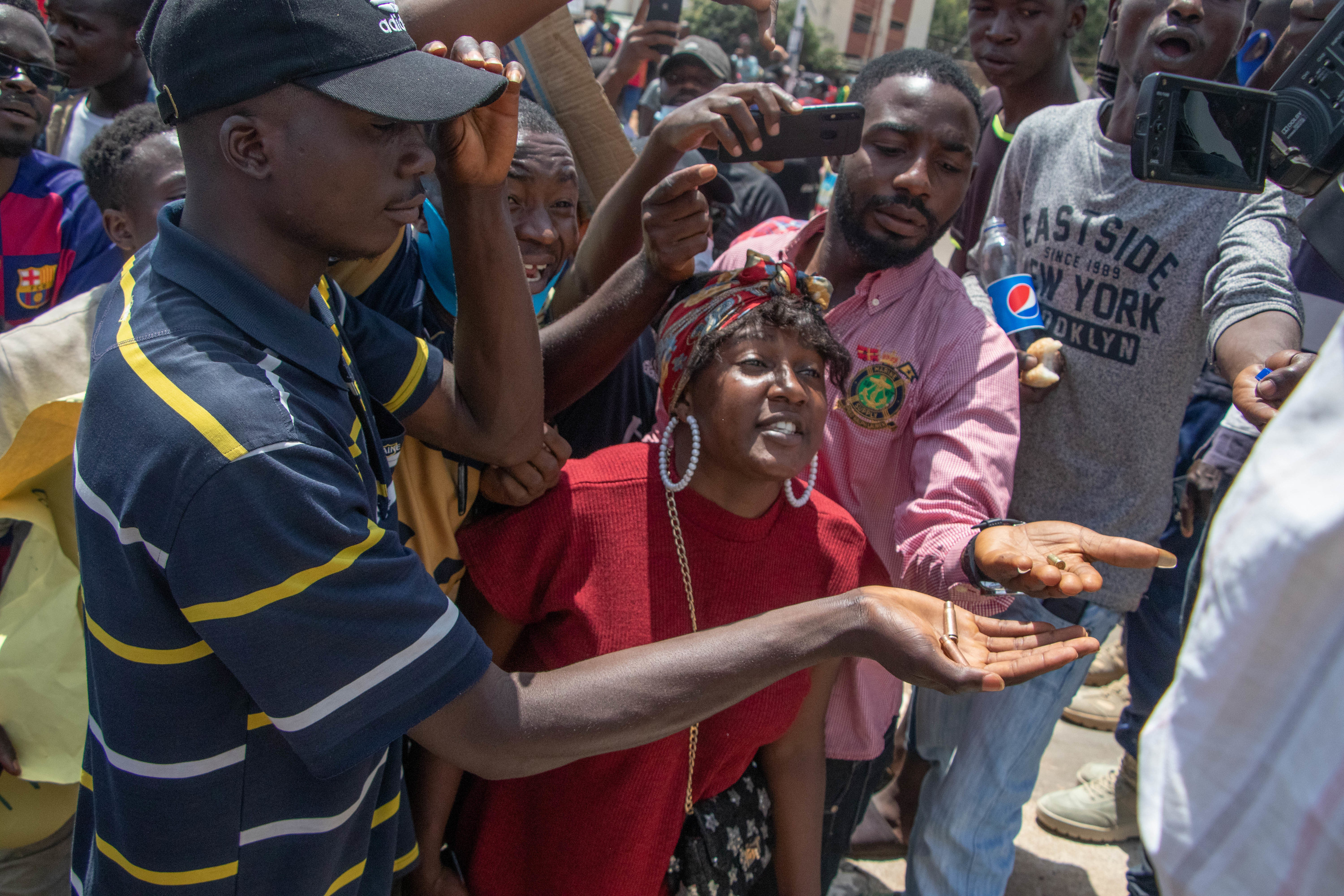 People hold bullets in outstretched palms while other people film on cellphones during a protest in Jos
