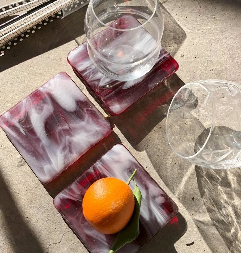 four handmade marbled coasters styled with drinking glasses and an orange