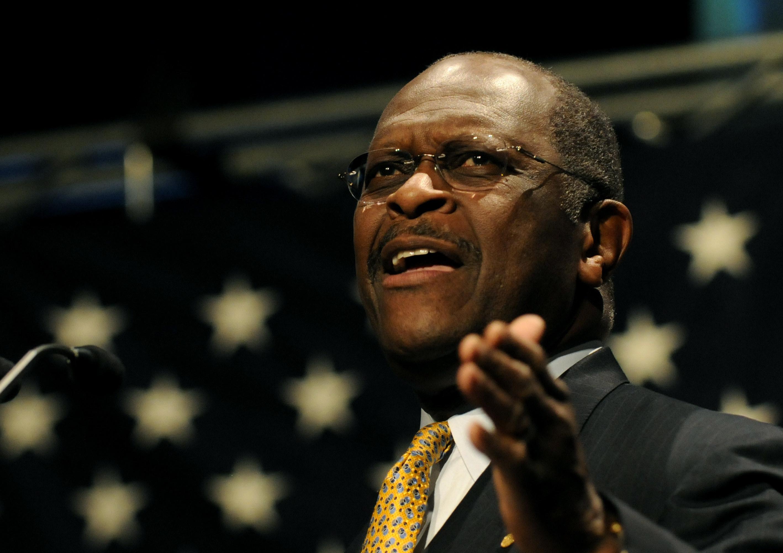 Cain onstage among stars, gesturing as he speaks