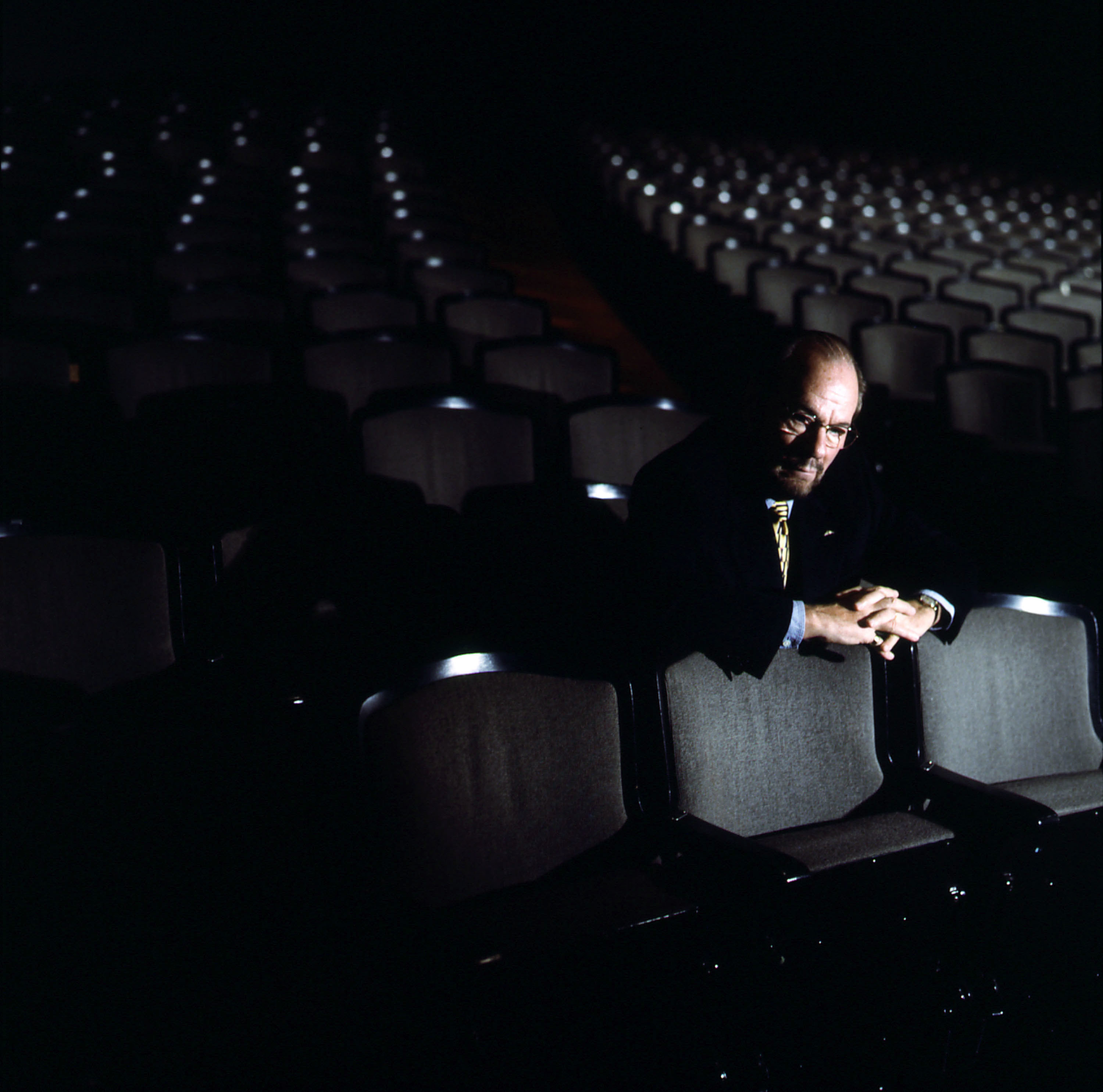 Lipton alone among many empty seats in a theater