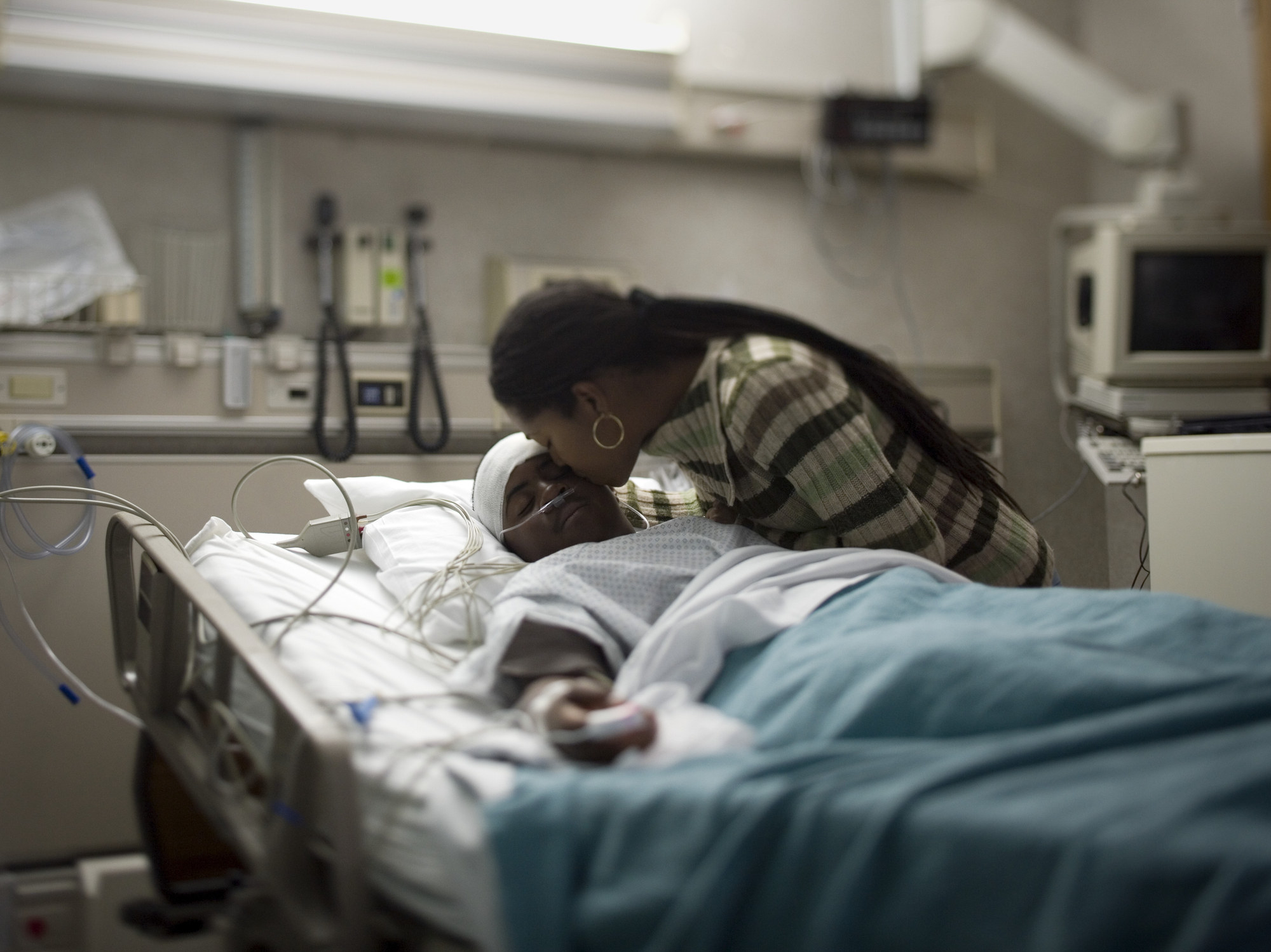 A woman kissing a young man in a hospital bed