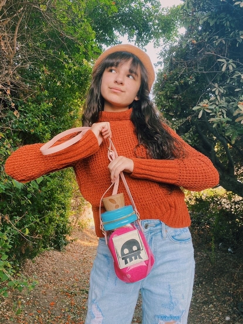 A model carrying the tall, thin crossbody bag shaped like a corked potion vial with details that make it look like it holds pink liquid and is labeled with the folded over llama label that could be easily confused for a skull