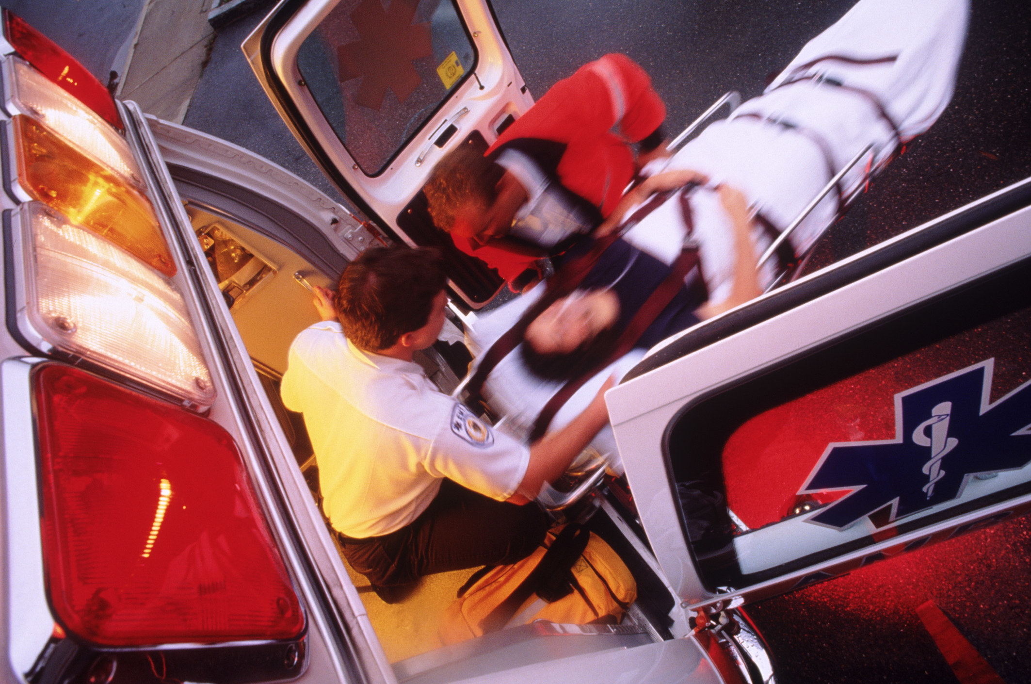 Ambulance workers loading a patient on a stretcher