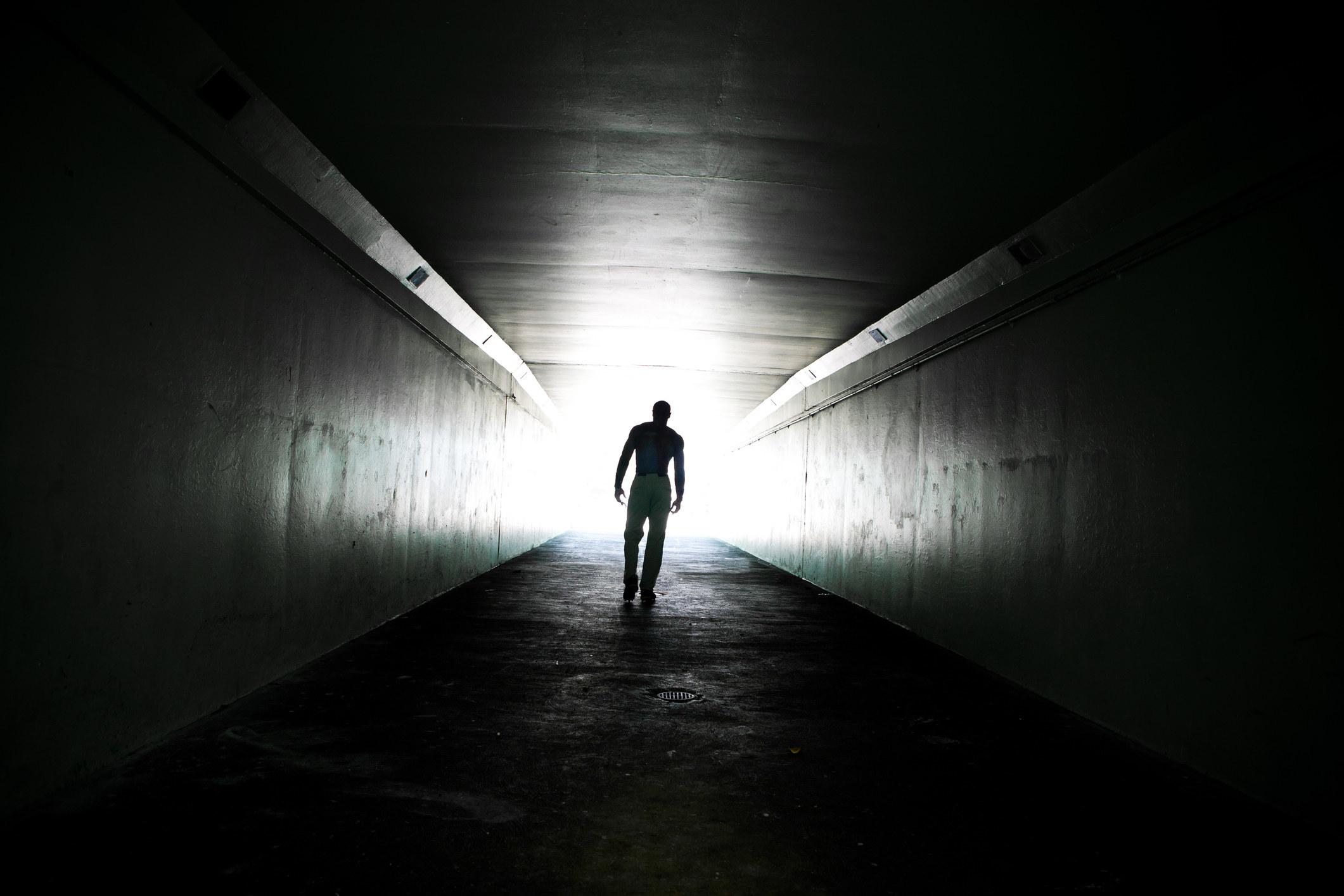 A person walking through a dark tunnel