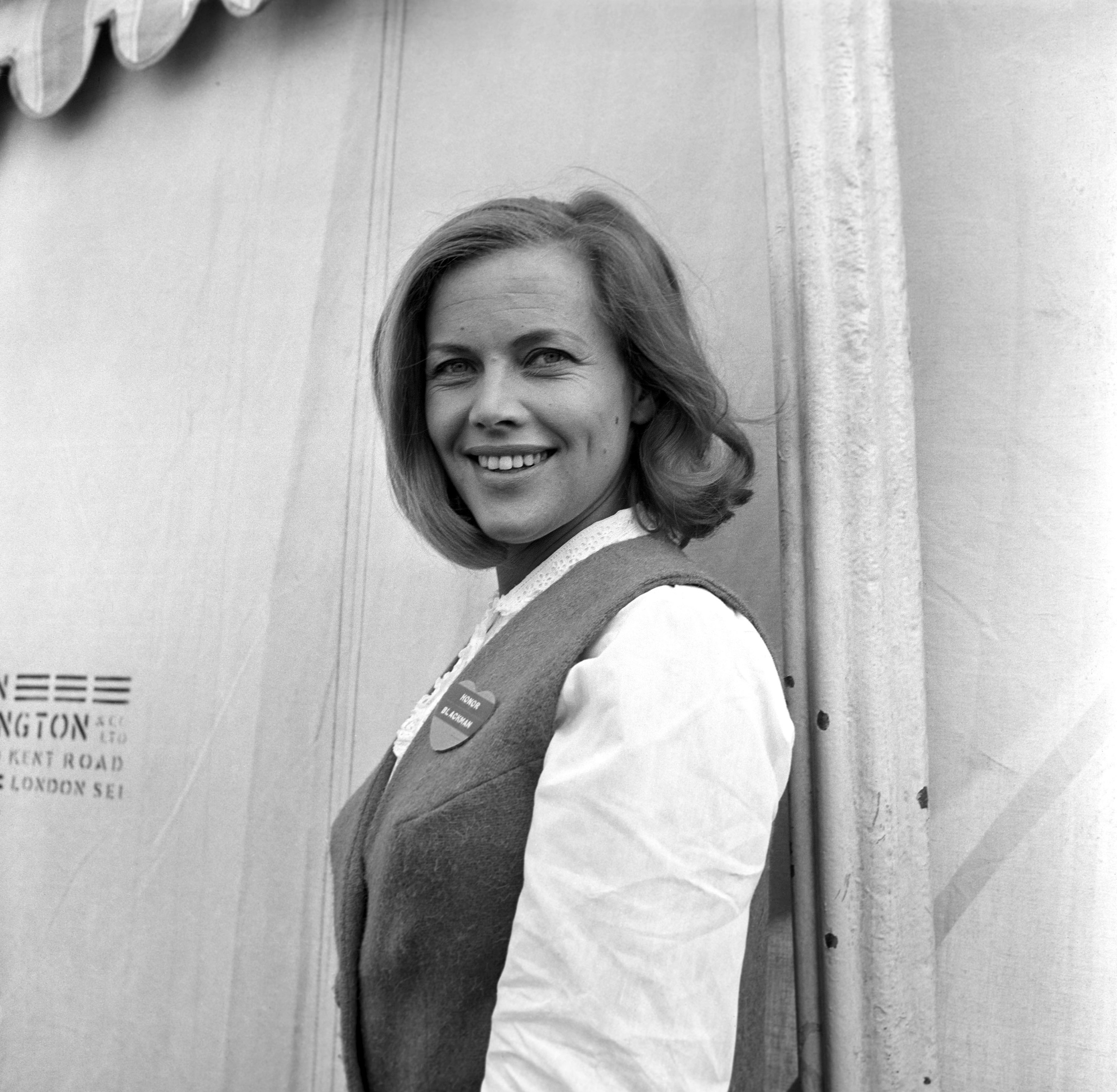 Honor Blackman in a vest on a movie set
