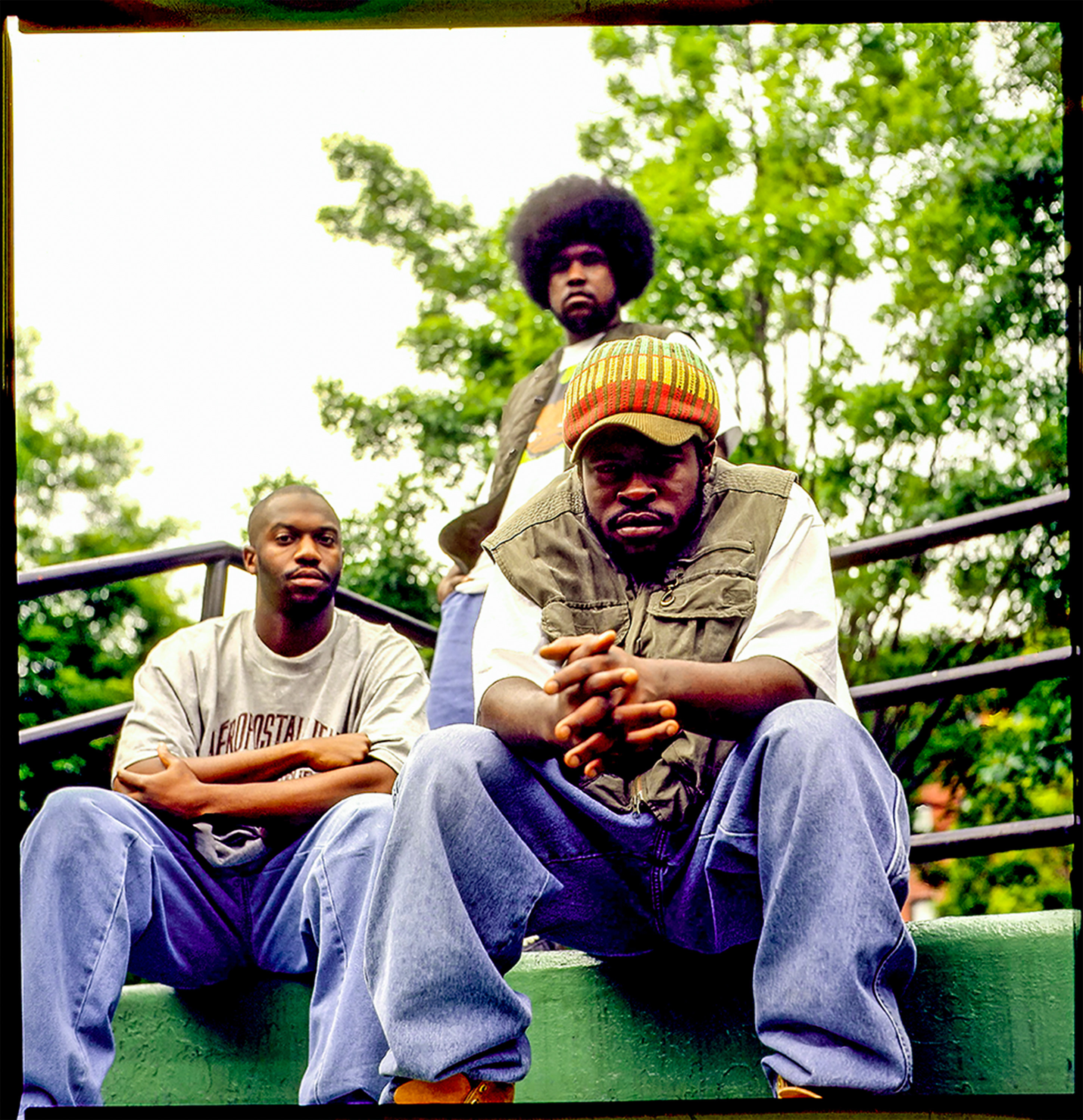 The three members of the Roots outside, looking at the camera, wearing t-shirts and jeans