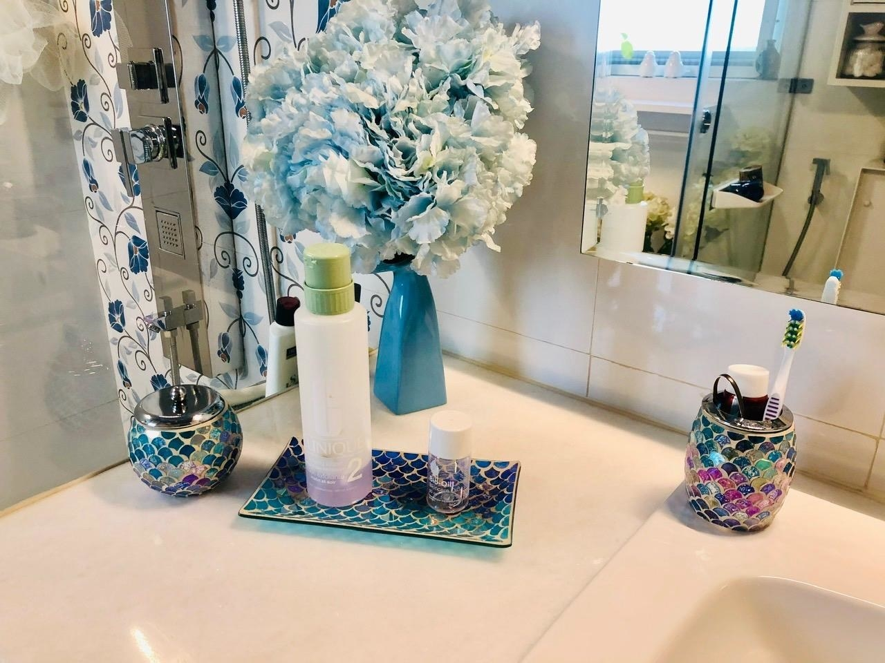 Reviewer's shimmery pink, blue, and green bathroom accessories set on a white counter