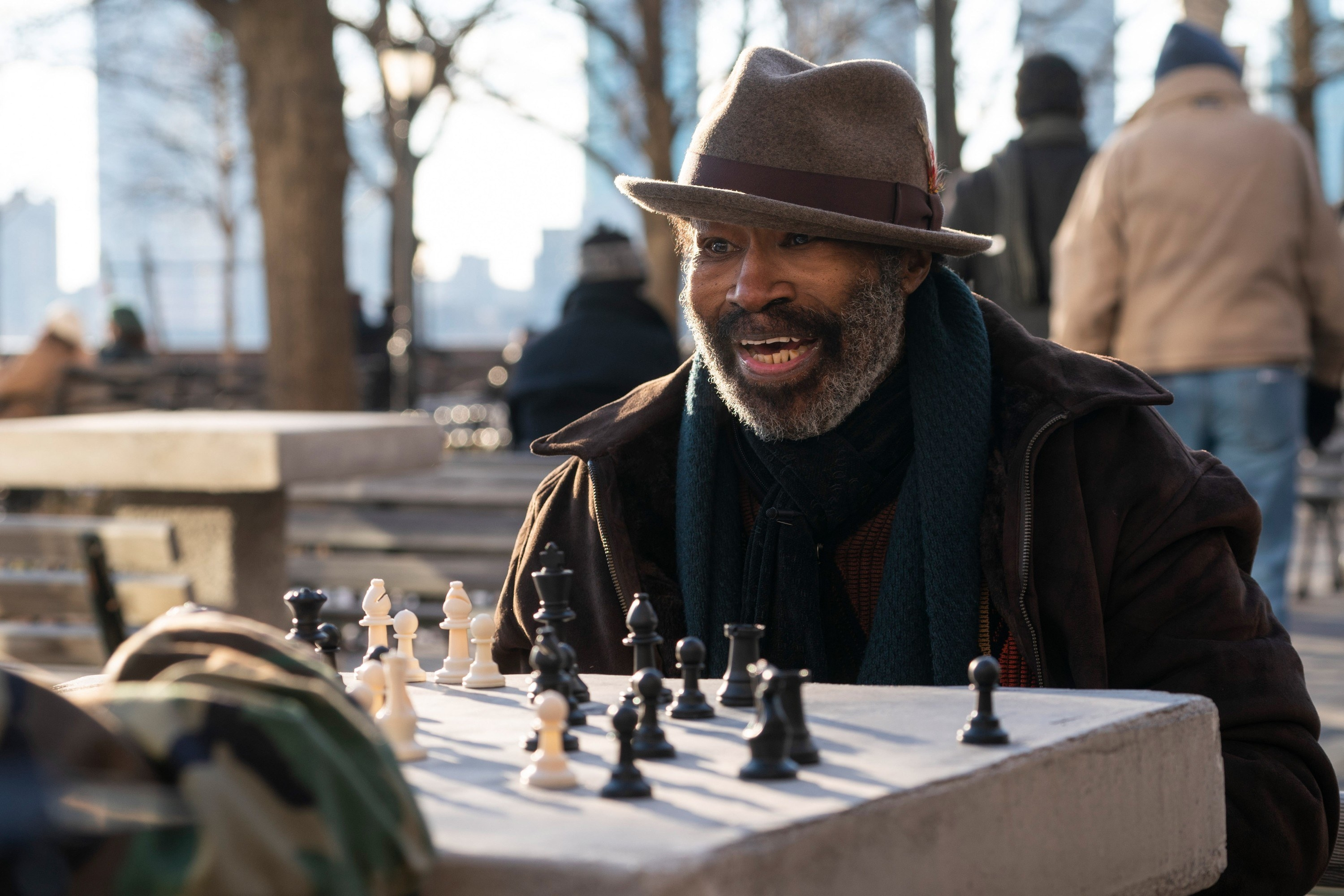 Chisholm in a fedora and jacket playing chess outdoors in NYC