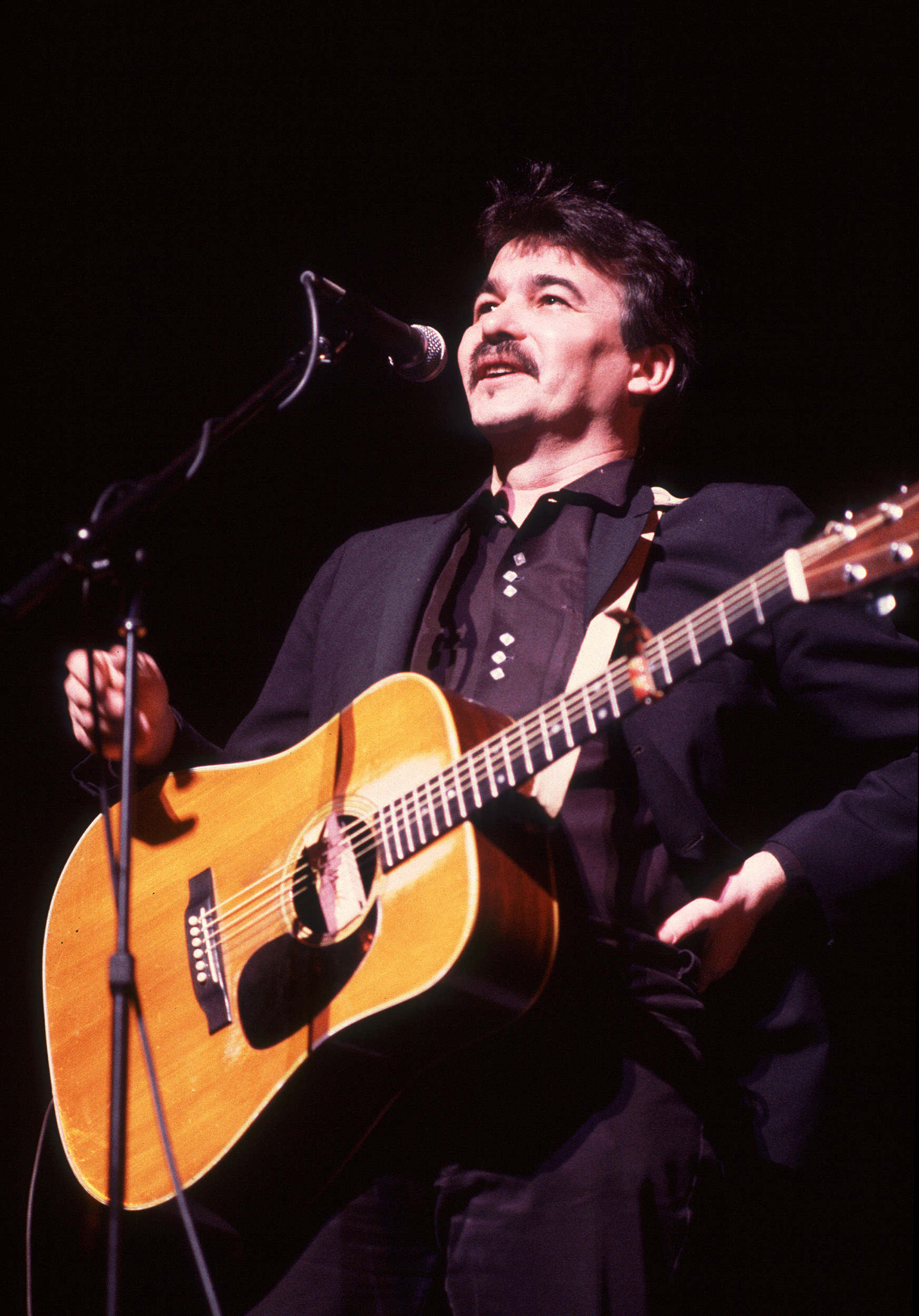 Prine on stage with bright lights on him holding a guitar