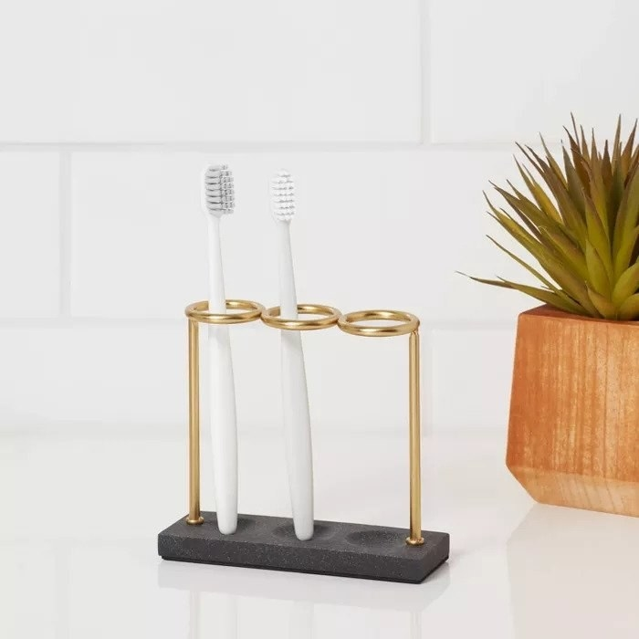 Gold toothbrush holder with three toothbrush slots on a white countertop