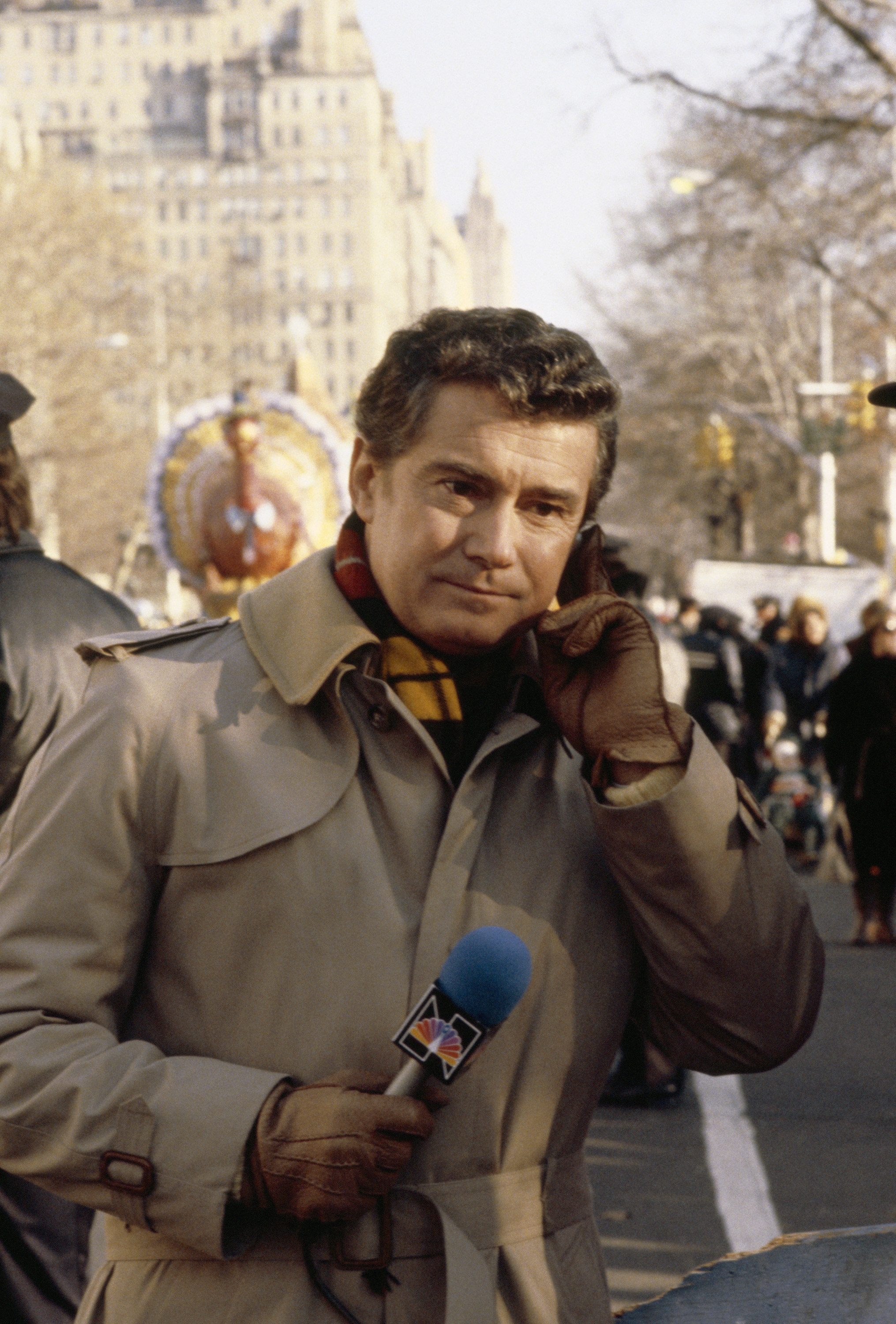 Philbin in a trench coat with a microphone during a parade
