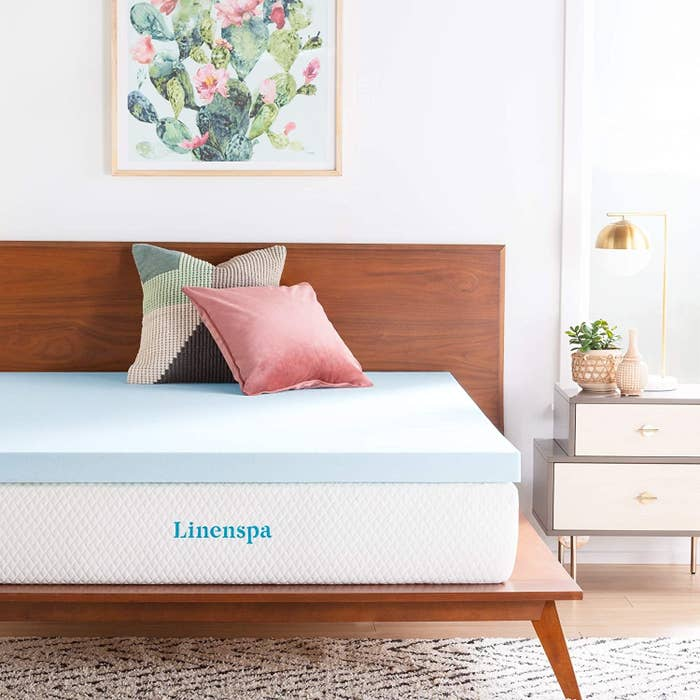 the memory foam mattress on top of a regular mattress with two pillows on a bed
