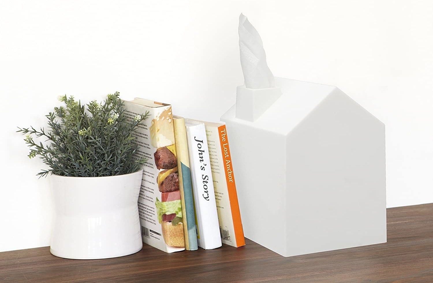 White house-shaped tissue box next to stack of books on a shelf