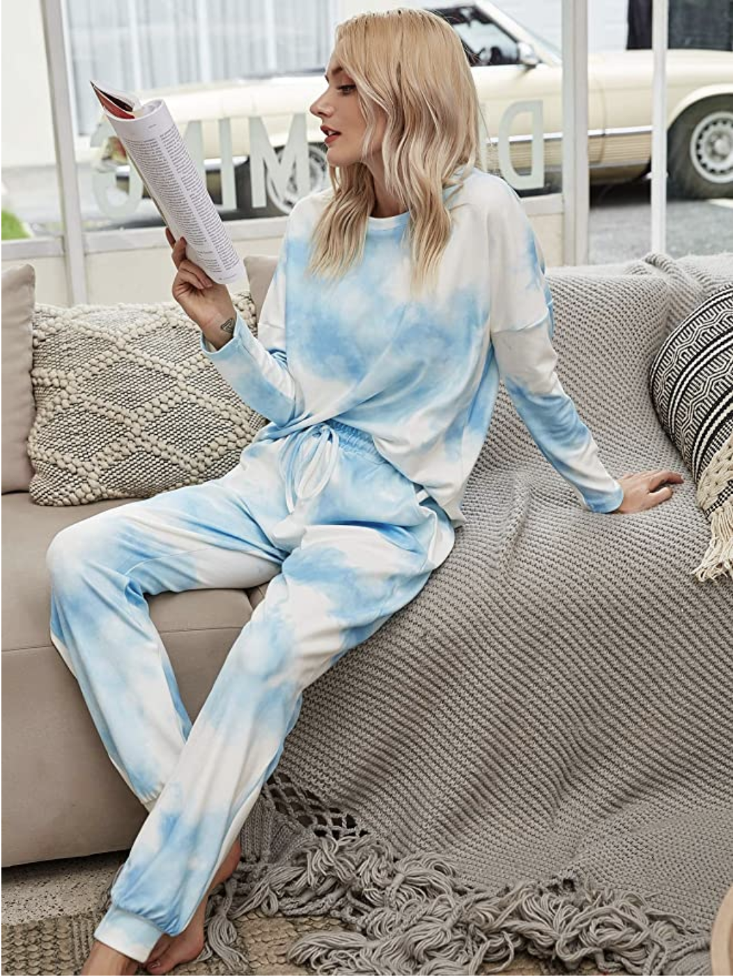 person wearing a tie dye pj set sitting on the couch reading a book