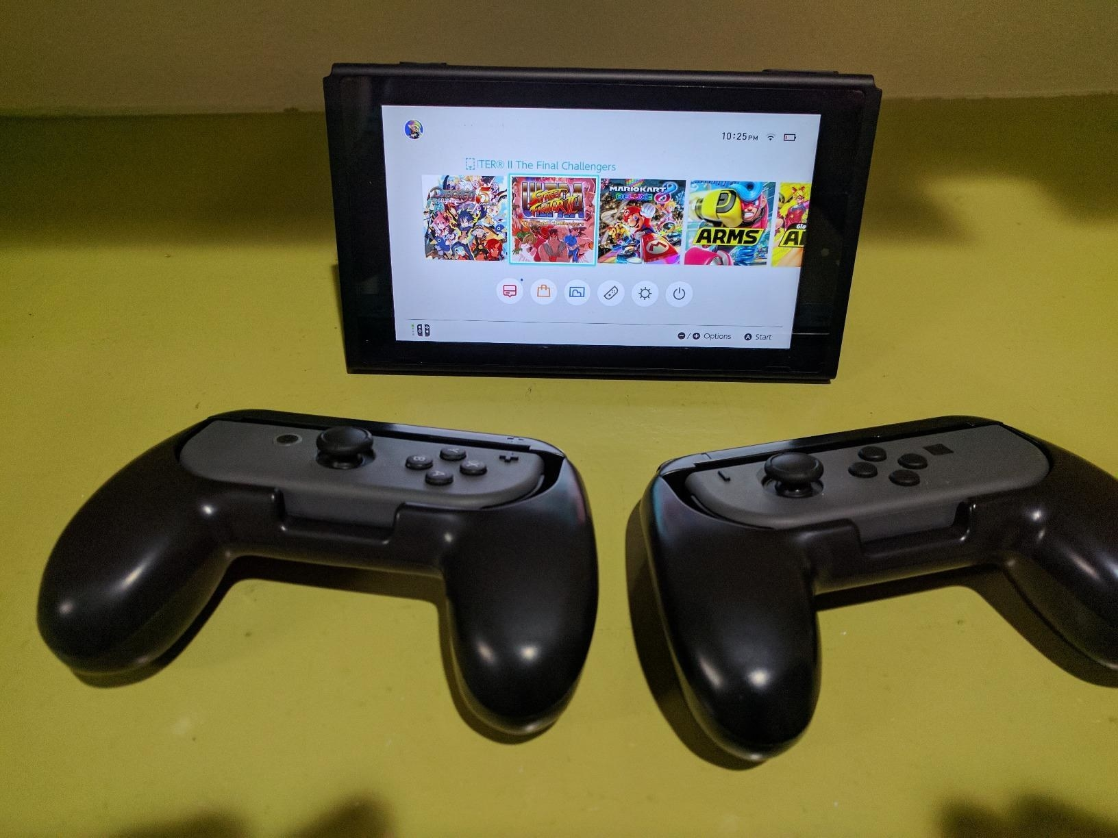 Two joy-cons controllers inserted into black joy-con grips