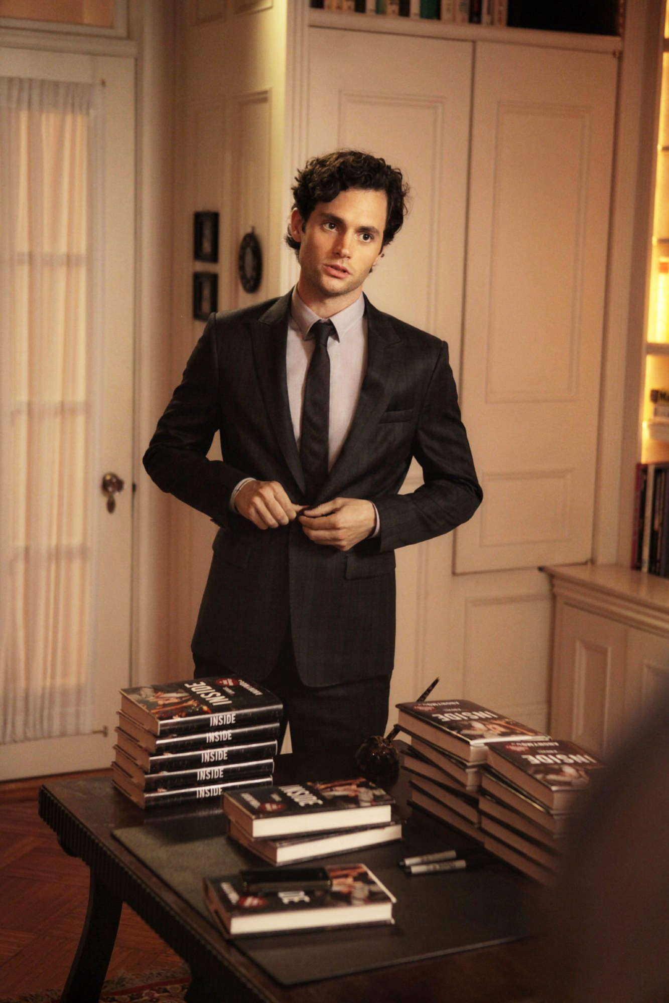 Dan Humphrey talking while buttoning up his suit
