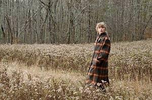 Taylor Swift walking through a field of wheat.