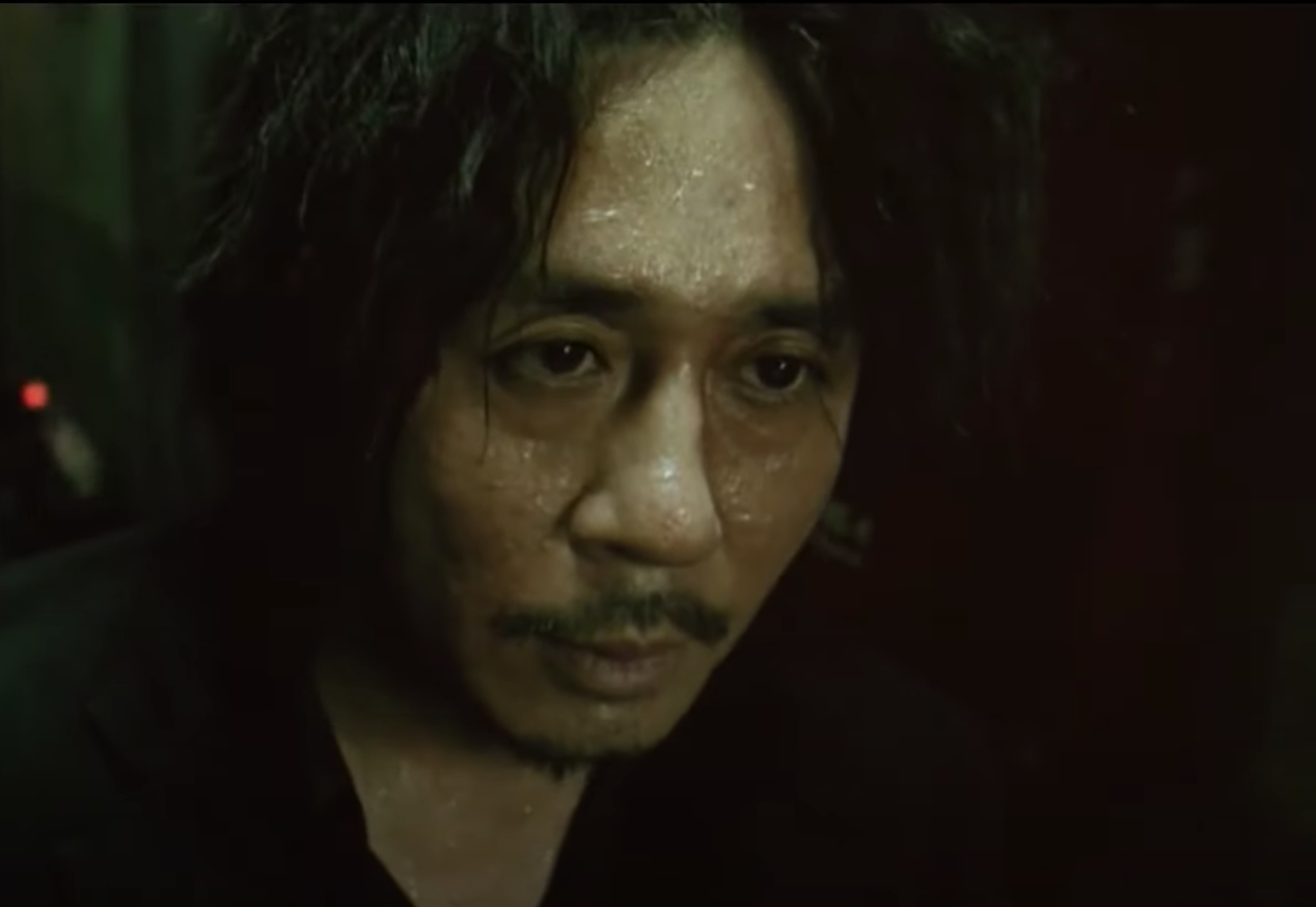 Dae-Su after a fight scene looking away from the crowd
