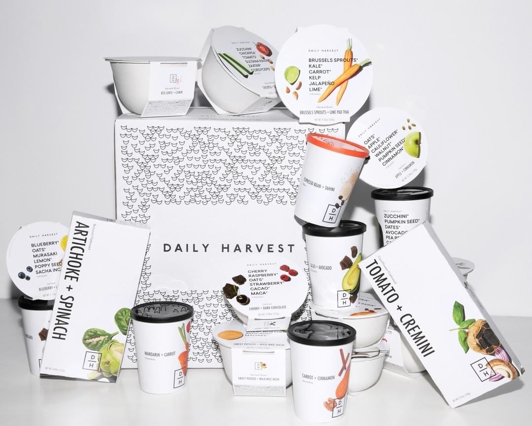 A white Daily Harvest box surrounded by an array of packaged smoothies, flatbreads, and harvest bowls
