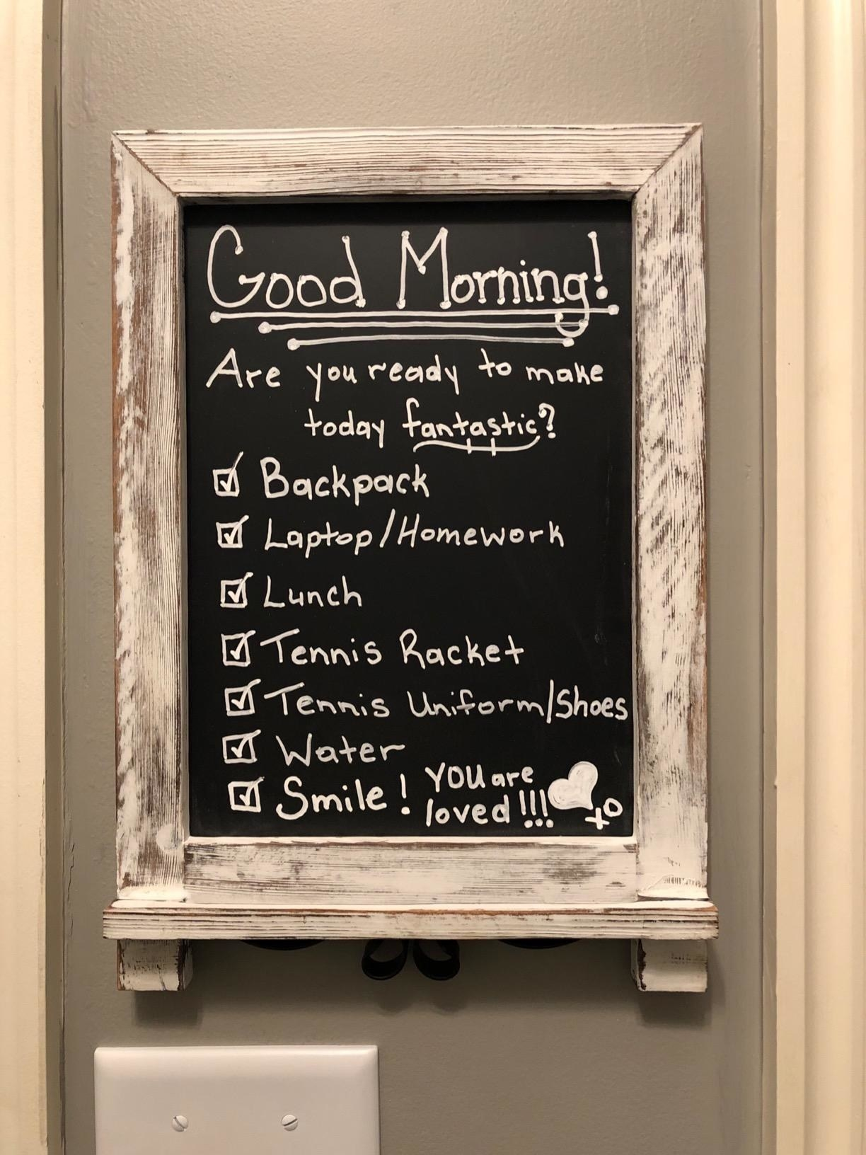 reviewer image of the rustic whitewash chalkboard mounted on a wall with a checklist on it