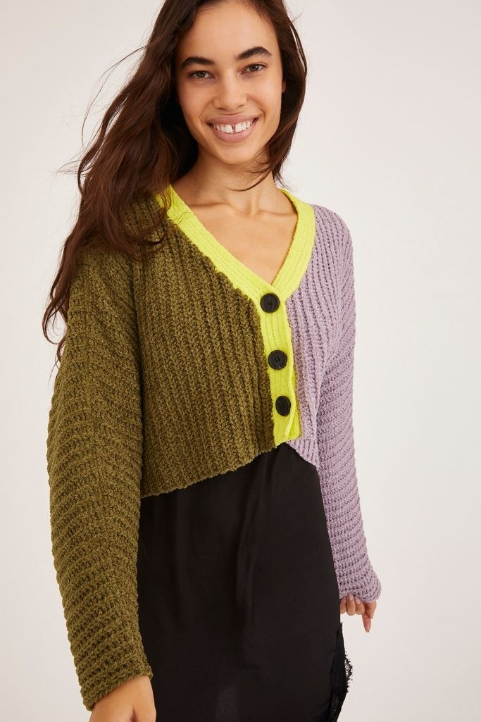 half purple, half olive sweater with three buttons and yellow collar