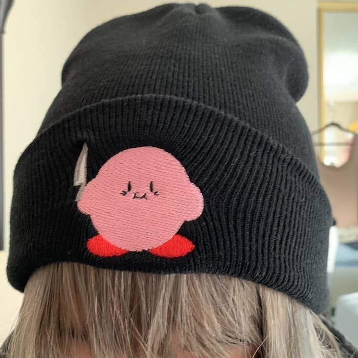 black beanie with patch of kirby holding a knife