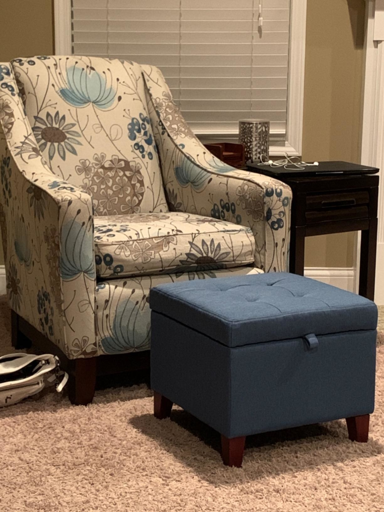 reviewer image of the deep blue adeco square storage ottoman in front of a floral armchair